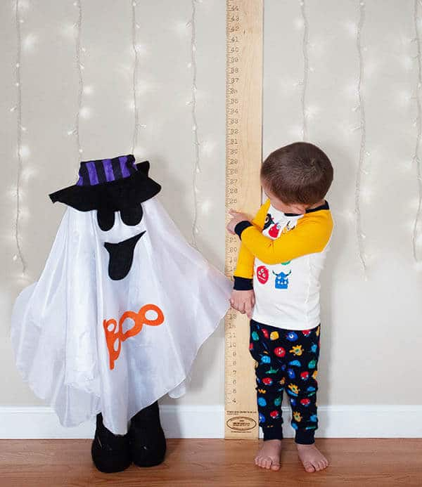Two children at Halloween standing in front of a wall with a ruler running up it